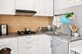 Niewielka kuchnia została zaprojektowana w białym kolorze, co optycznie rozjaśnia i powiększa wnętrze