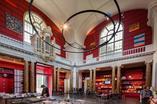 Wnętrze historycznej kaplicy z czerwonymi półkami, na których są poukładane programy muzeum.