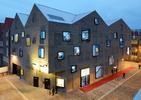 Okna oświetlone LED czy ekrany multimedialne na elewacji z cegły? Myląca architektura współczesna bryły Poppodium Venlo