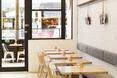 Widok na wejście i wieszaki z prasą w restauracji Lucky Penny w Melbourne.