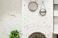 Biały kominek i trzy okrągłe lustra na ścianie w restauracji Lucky Penny w Melbourne.