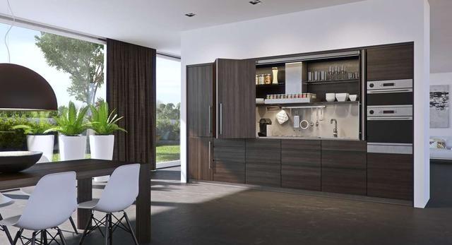Bryła mebla zajmującego ścianę salonu, to mała kuchnia ze wszystkimi niezbędnymi elementami.