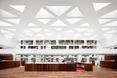 Drewniana podłoga kontrastuje z ażurowym sufitem z trójkątnych otworów  autor: holenderska pracownia KAAN Architecten